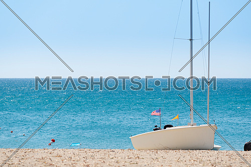 anchored boat with american flag on sandy beach and blue sea, sunny day ,Summer vacation concept.