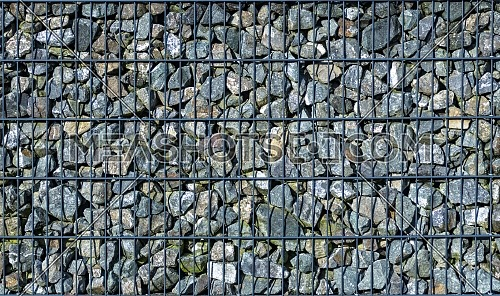 A modern form of house fencing. Gabions, steel galvanized nets filled with split stone.