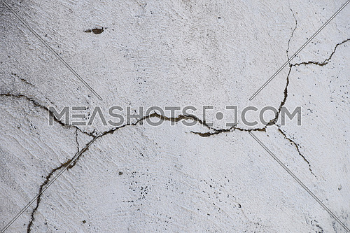 Damage split crack in white painted plaster concrete wall background
