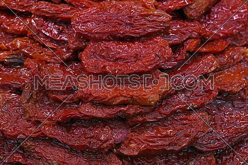 Sundried cured red tomatoes on retail fresh food market stall display, close up, high angle view
