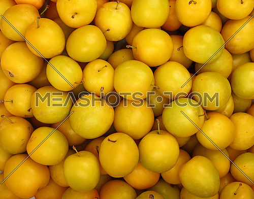 Fresh ripe mellow yellow plums (cherry plums) background pattern close up, top view