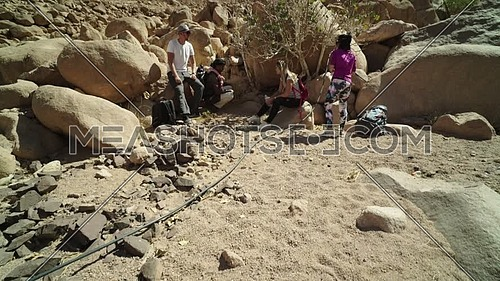 Follow shot for group of tourists get rest in the shade besides Almond tree with bedouin guide to explore Sinai Mountain for wadi Freij at day.