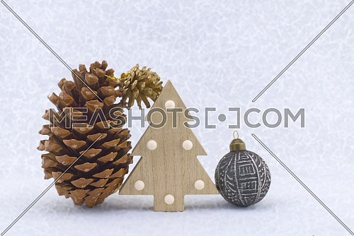 Cedar cones and a stylized wooden Christmas tree against a snowy background