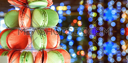 French colorful macarons tower Multicolor macaroon on christmas bokeh light abstract holiday background Sweets. Food background.
