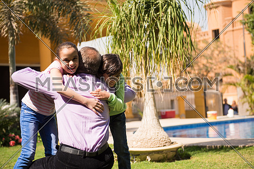 happy middle eastern grandfather enjoying with their grandchildren in the yard of a beautiful sunny day
