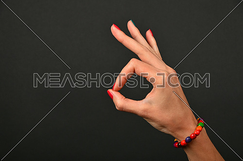 Woman hand with colorful wooden painted beads bracelet shows ok okay gesture sign over black background