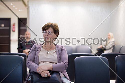 portrait of senior middle eastern woman with other people waiting for the doctor in hospital lobby