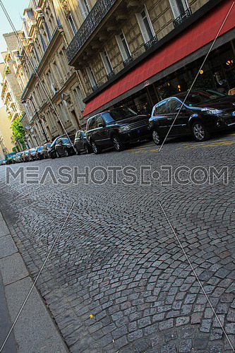 Street tiles in Paris allies with black cars parked on the side of the road