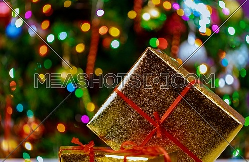 Detail of a christmas present and christmas tree decorations lights and gift boxes selective focus