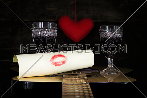 Happy Valentine's Day Kiss On White Paper Resting on Acoustic Guitar With Vine Glasses, Lights and Heart