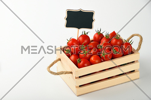 Fresh red ripe cherry tomatoes in small wooden box with black chalkboard price sign tag over white background