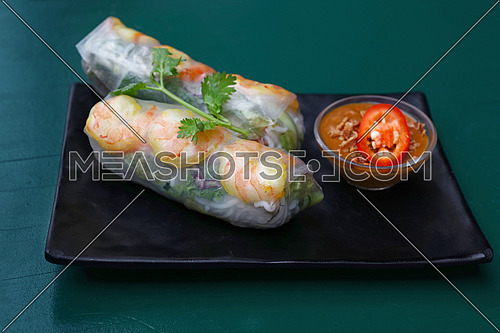 Close up portion of two fresh spring rolls with shrimps and dipping chili sauce on plate over table, high angle view