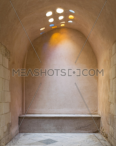 Arched stone wall lighted by colored circular shaped roof holes at a historical traditional Turkish style bath (Hamam Inal), Medieval Cairo, Egypt