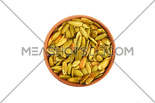 Roasted pumpkin seeds in wooden bowl top view on white background
