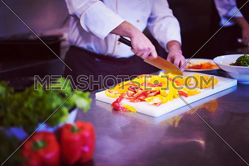 Chef cutting fresh and delicious vegetables for cooking or salad