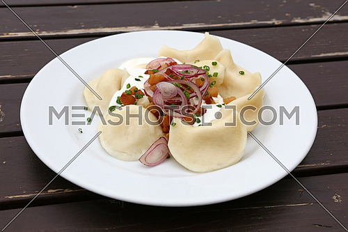 Plate of pierogi or varenyky stuffed filled dumplings with sour cream, bacon and onion, traditional East Europe cuisine meal popular in Poland, Ukraine, Slovakia and Russia, close up, high angle view