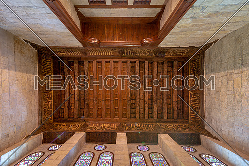 Wooden ornate ceiling with floral pattern decorations and colorful stained glass windows at Sultan al Ghuri Mausoleum, Cairo, Egypt