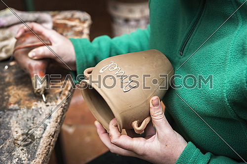 Potter decorating a ceramic jar with the word honey, clay pottery ceramics typical of Bailén, Jaen province, Andalucia, Spain