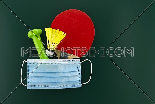 Dumbbells, shuttlecock, table tennis racket cover with a medical face mask. Sports during the quarantine period concept with free copy space