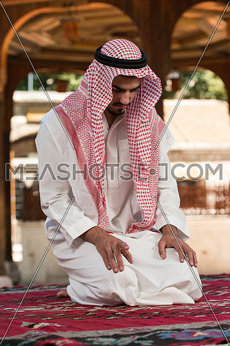 Young Muslim Man Making Traditional Prayer To God While Wearing A Traditional Cap Dishdasha