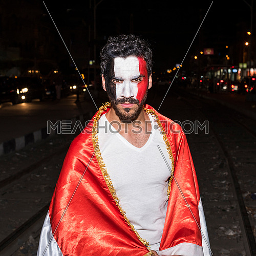 young man cover himself with big egyptian flag and has a paint for egyptian flag on his face in korba area at night