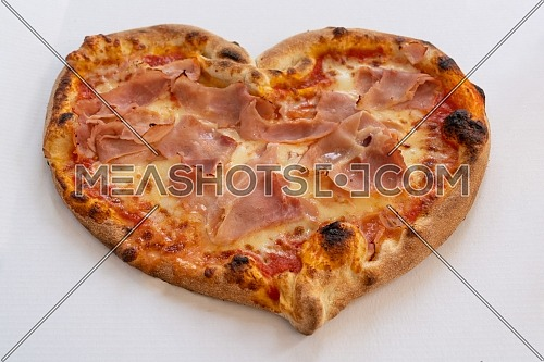 Heart shaped pizza with tomatoes and ham for Valentines Day on white cardboard background,Food concept of romantic love