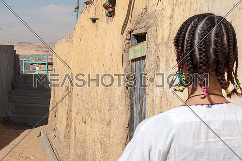 A nubian girl from behind standing in an alley