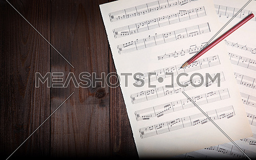 In the picture aged pages of sheet music, pencil  and wooden background, above view.