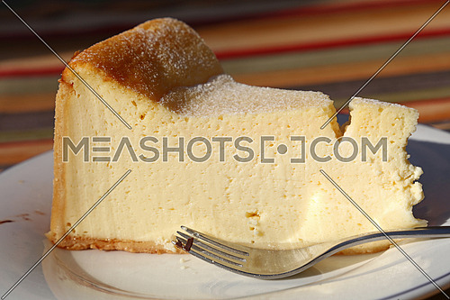 Slice of fresh traditional souffle cheesecake on white plate with fork on table, close up, low angle side view,
