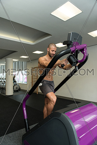 Handsome Man Exercising On A Stepper In Gym