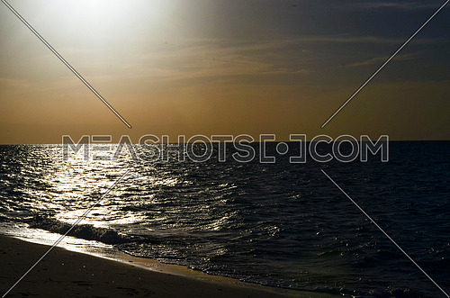 Sunset magical golden hour by the beach and sun reflection appears on water