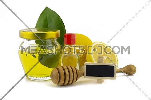Honey and lemon still life for healthy diet concept with a wooden wand leaning on a glass jar of honey against green leaves and fresh halved juicy lemon over a white background