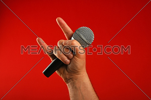 Man hand holding voice microphone with devil horns rock metal gesture sign over red background, diagonal