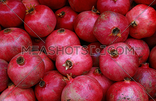 Fresh red ripe pomegranates at retail market stall display, close up, elevated high angle view