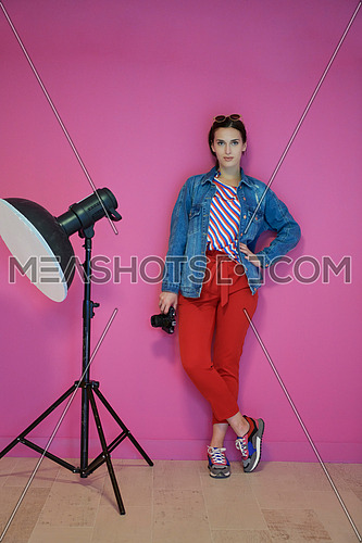 Female photographer holding camera in her hand and leaning against pink wall. Professional photography equipment in the studio