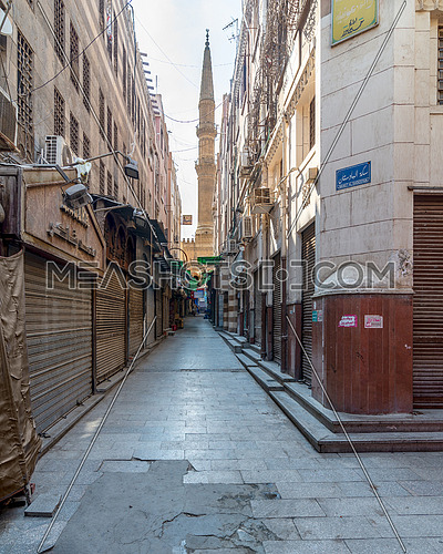 Cairo, Egypt- June 26 2020: Alley in old historic Mamluk era Khan al-Khalili famous bazaar and souq, with closed shops, and minaret of Al-Hussein Mosque in the far end, during Covid-19 lockdown