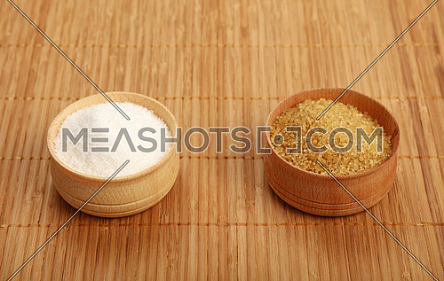 Choice, selection of two sugars in small full wooden bowls on bamboo mat background, brown cane and white sugar