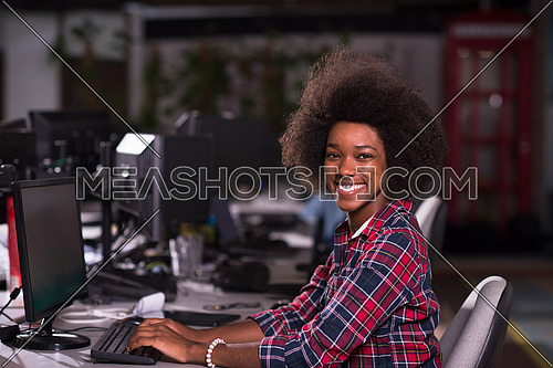 portrait of a young successful African American woman who enjoys while working in a large modern office