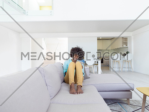 Young african american woman at home relaxing in her luxury lliving room reading a digital tablet  surf internet and work
