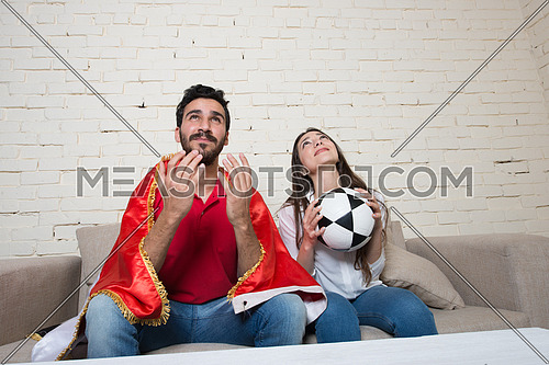 A young couple watching football match in living room