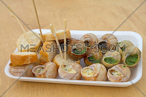 Close up street fast food take away portion of cooked escargot snails with French herbs and garlic butter and baguette bread, high angle view