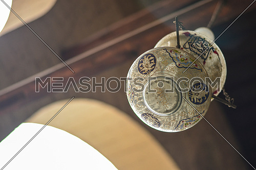 A ceiling lamp with islamic writings hanged in an old mosque