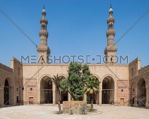 Courtyard of Mamluk era al Nasir Faraj ibn Barquq public historical mosque with minarets of the mosque, Al Darb Al Ahmar district, Cairo, Egypt