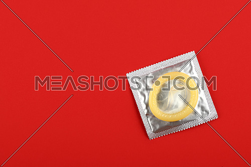 Close up one latex condom on silver wrap pack over vivid red background with copy space, elevated high angle view, directly above