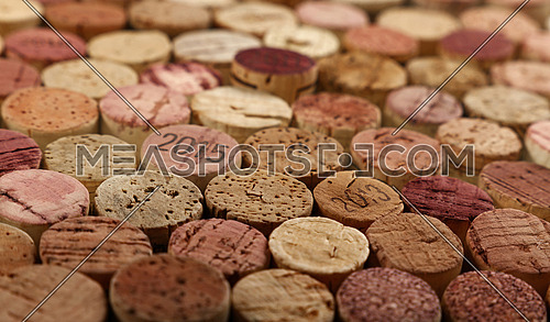 Close up background pattern of many assorted stacked used red wine corks, high angle view