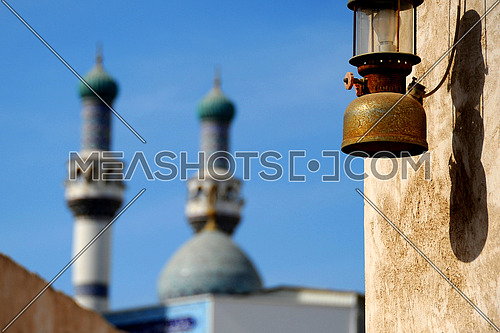 oil lantern hanged on the wall with mosque in the background