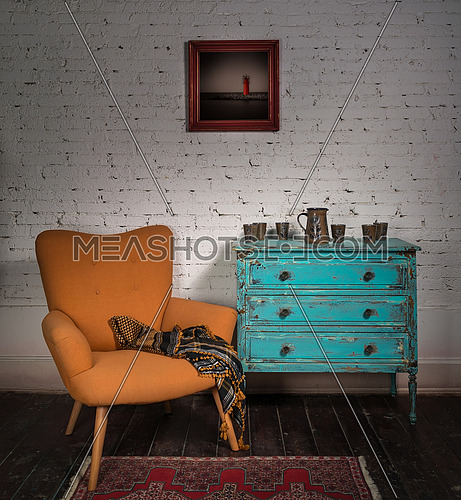 Composition of vintage orange armchair, blue cabinet, hanged painting and ornate scarf in studio