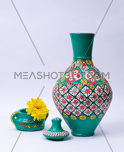 Still life of green ornate pottery vase, lid, green pottery cup and yellow flower on white background
