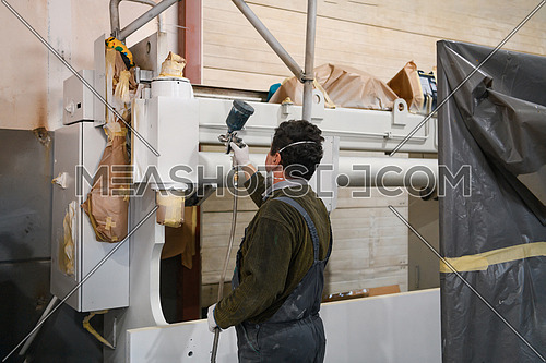 A worker painting to mechanical part with airless spray. High quality photo