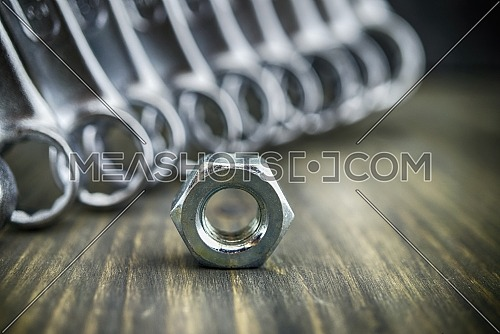 Single metal nut from a bolt with set of spanners in a diagonal line behind and focus to the nut